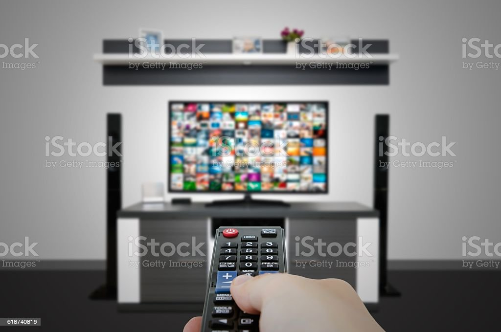 Watching television in modern TV room. Hand holding remote stock photo