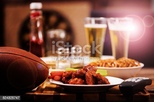 Chicken hot wings and football in foreground.  Beer in mugs in background with television.  Local pub or sports bar.  Dartboard in background.  Bar top. Superbowl party! Lens flare from television screen.