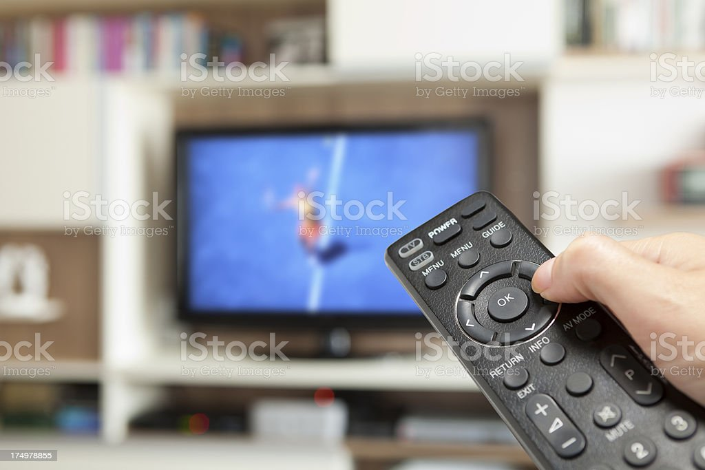 watching tennis with TV remote control in hand royalty-free stock photo