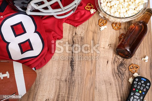 Football season is here.  Concept of sports fan watching the game on TV at home, at tailgate party, or sports bar with snacks and drinks.  TV remote, popcorn, football, jersey, helmet and beer bottle.