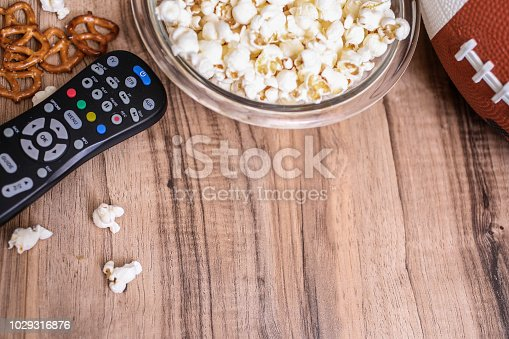 Football season is here.  Concept of sports fan watching the football game on TV at home, at tailgate party, or sports bar with snacks and drinks.  TV remote, popcorn, football and soda, beer bottles.  Superbowl party.