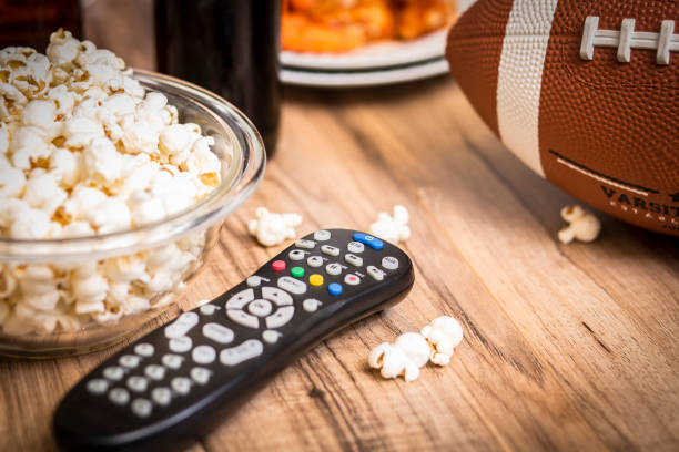 watching the football game with snacks, drinks. - telecomando background foto e immagini stock