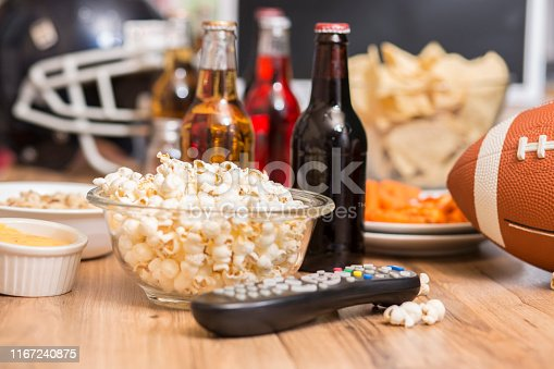 Football season is here.  Concept of sports fan watching the game on TV at home, at tailgate party, or sports bar with snacks and drinks.  TV remote, chips, football and soda, beer bottles.  Superbowl party.