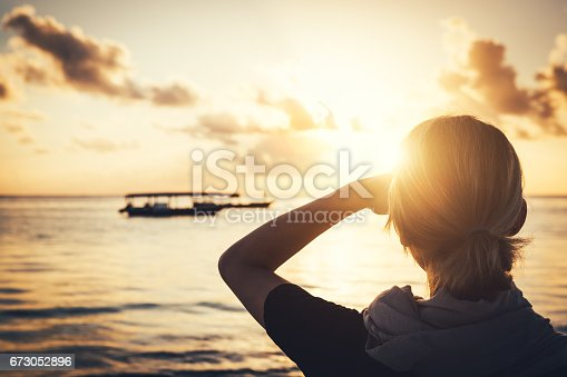 Rear view on young woman watching sunrise at Pwani Mchangani beach (Zanzibar, Tanzania, Africa).