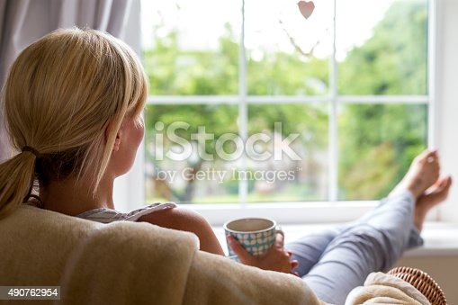 A young woman sits with a hot drink and her feet up, watching out of the window from the comfort of her own home. She is taking a break from her chores and busy day to day routine to gaze into her garden and wonder.
