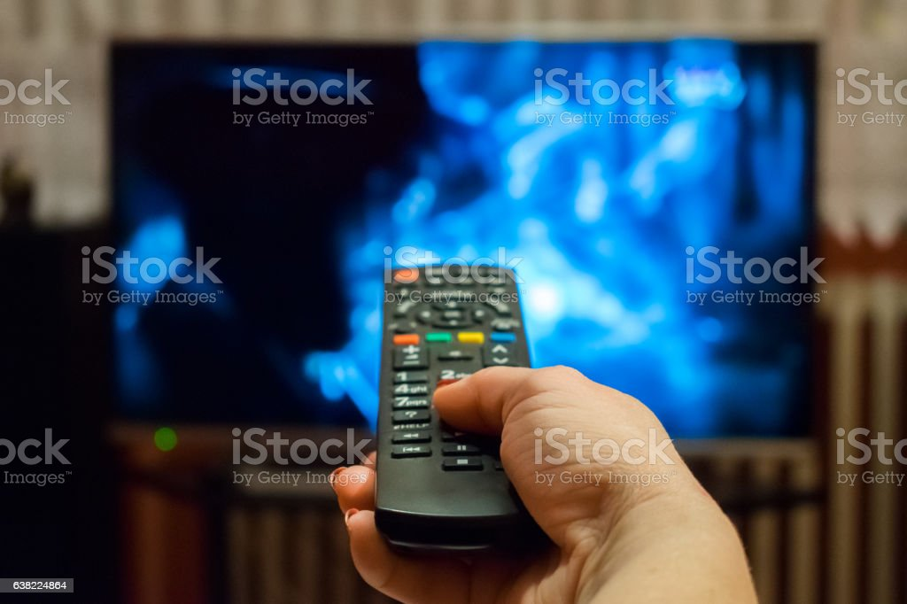 Watching tv and using remote control Watching tv and using remote control Bandwidth Stock Photo