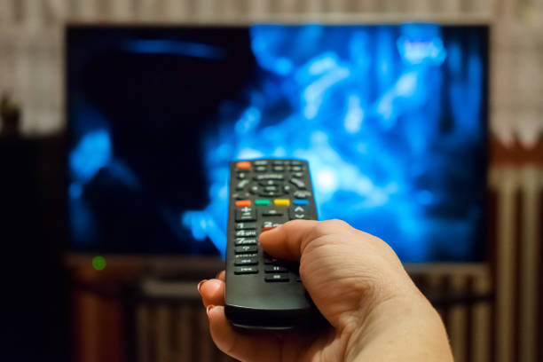 Watching tv and using remote control stock photo
