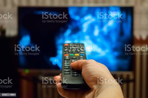 Watching Tv And Using Remote Control Stock Photo - Download Image Now