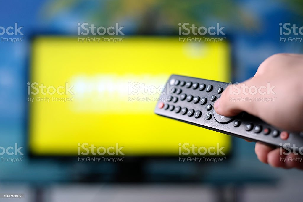 Watching TV and using remote controller stock photo