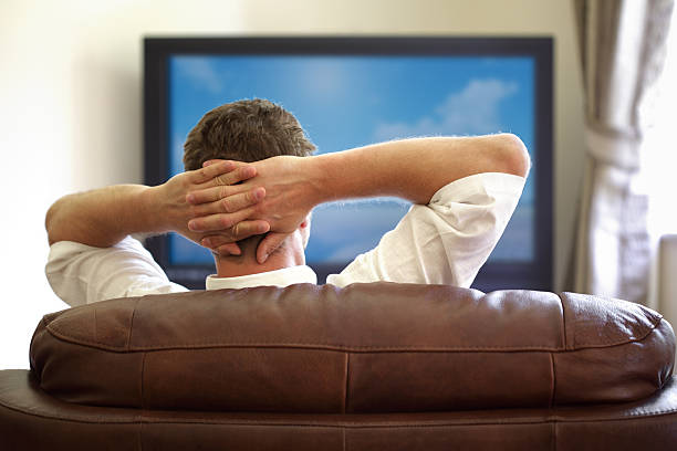 Watching tv Man sitting on a sofa watching tv with hands folded behind his headPlease see similar picture from my portfolio: cable tv stock pictures, royalty-free photos & images