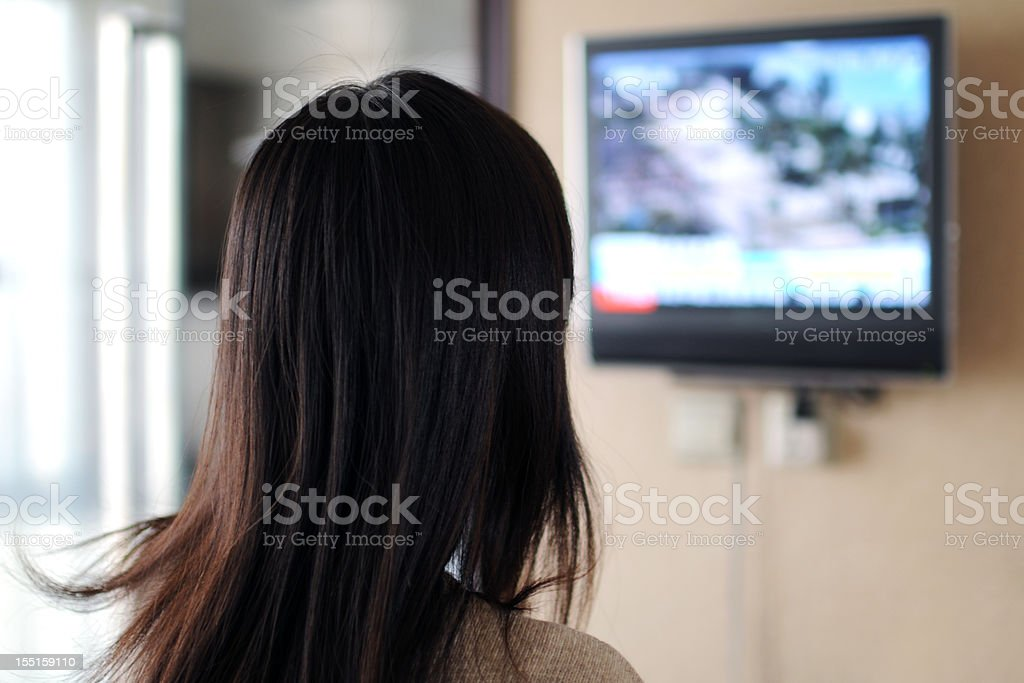 Watching TV - XLarge Asian woman is watching news Accidents and Disasters Stock Photo
