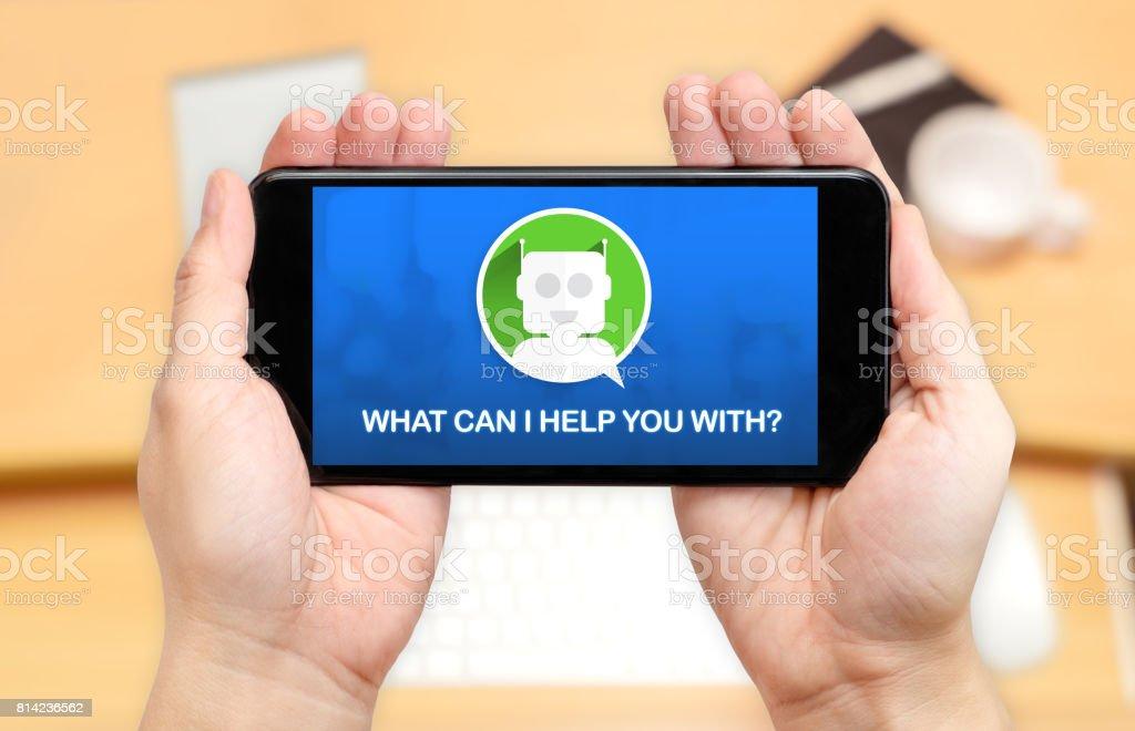 Gerade zwei Hand Holding Handy mit Chat-Bot und was kann ich Ihnen helfen? mit Unschärfe Schreibtisch Büro Hintergrund, Digital Marketing-Konzept – Foto