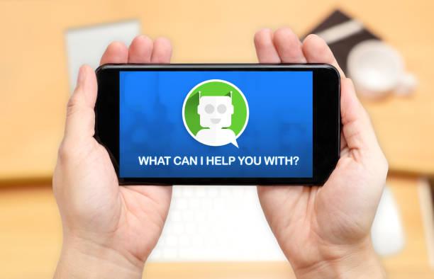 je regarde les deux main portefeuille mobile phone avec chat bot et ce que je peux vous aider avec? avec fond de flou bureau bureau, le concept de marketing numérique - chatbot photos et images de collection