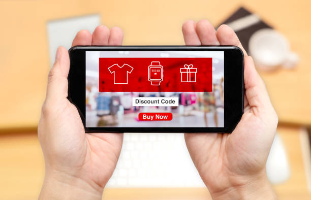 Watching two hand holding mobile phone with online shopping store and discount code on screen with blur desk office background,Digital lifestyle concept Watching two hand holding mobile phone with online shopping store and discount code on screen with blur desk office background,Digital lifestyle concept. discount store stock pictures, royalty-free photos & images