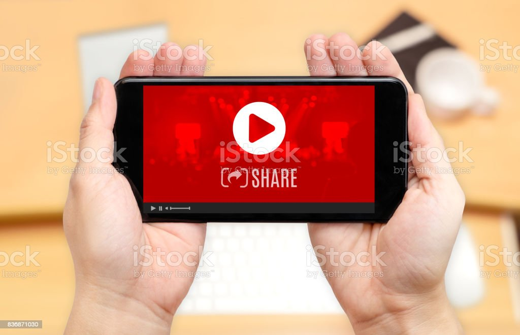 Watching two hand holding mobile phone with play and share icon on screen and blur desk office background,Digital content concept stock photo