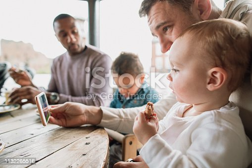 Father entertaining his baby son with videos on a smartphone as they eat breakfast.