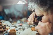 watchmaker repairing watch at his workshop . looking through jewelry monocle