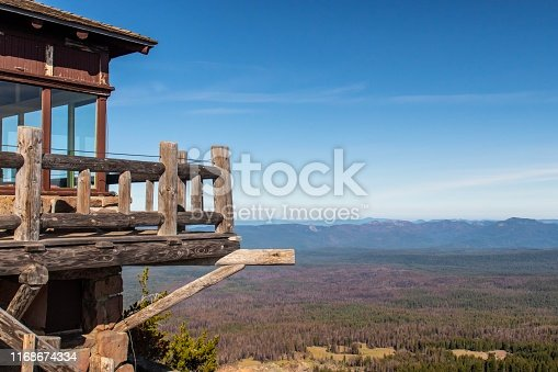 The Watchman Lookout tower at Crater Lake National Park is still used as a fire lookout station at times. Visitors can hike to the base of the structure to take in the sweeping views.  Brown trees show the devastation caused by recent wildfires.