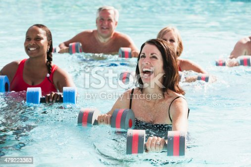 Group of mature people (50s, 60s) in swimming pool, doing water aerobics exercise class.  Focus on woman in foreground.