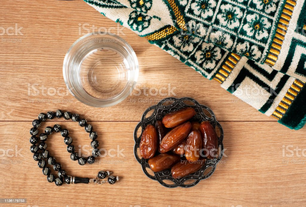 Water and dates. Iftar is the evening meal. View of decoration Ramadan Kareem holiday carpet background stock photo