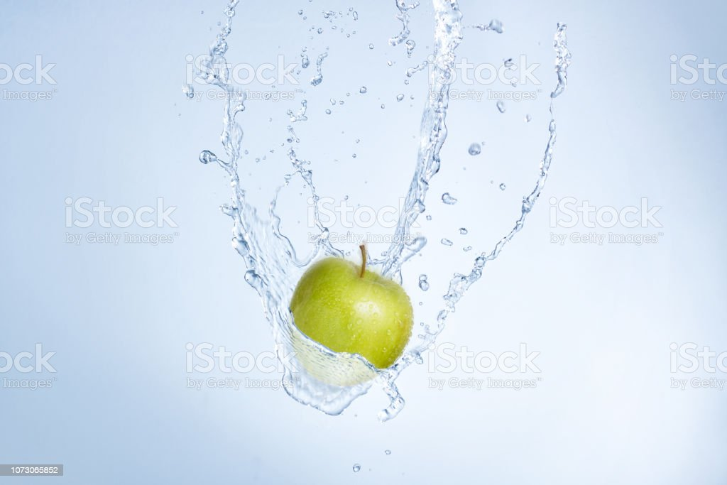 Fresh cold water splash with a green apple falling through.