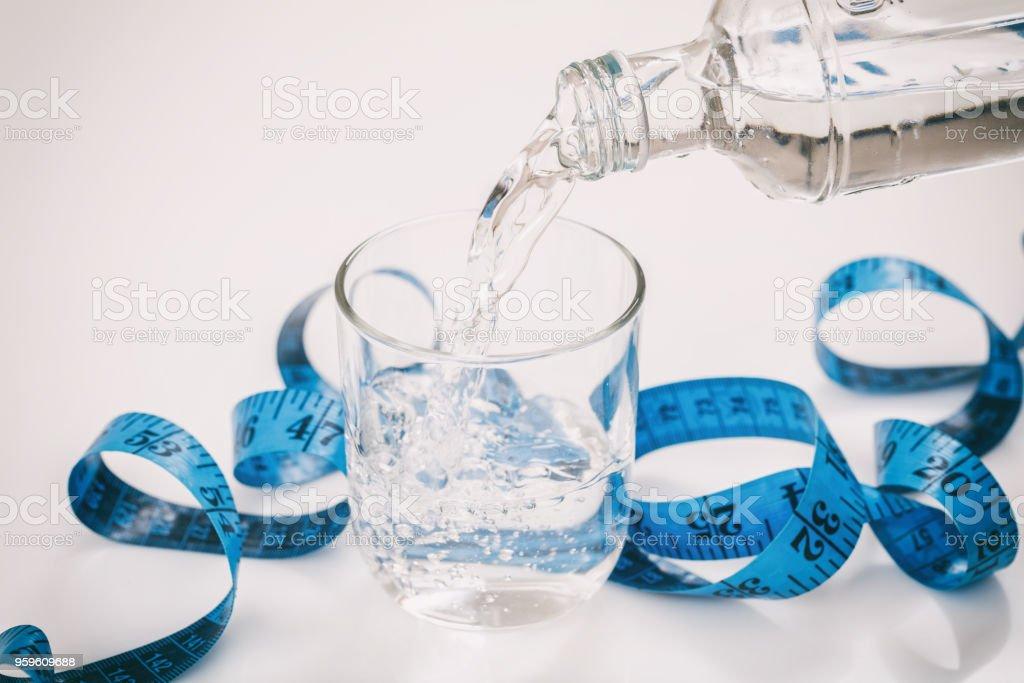 Agua y la cinta métrica sobre fondo blanco - Foto de stock de Agua libre de derechos