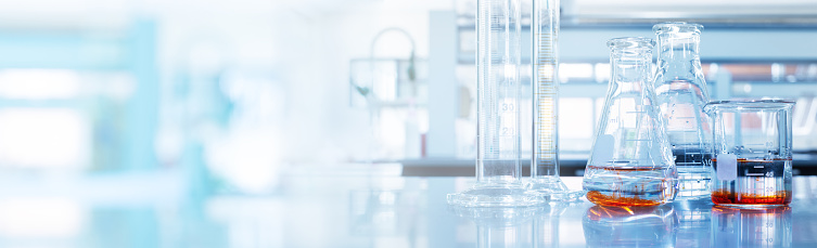 water and orange solution in glass flask and cylinder in soft blue light reseach medical science laboratory banner background