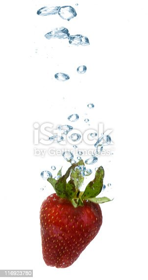 Strawberry is falling down to water and water is splashing out.