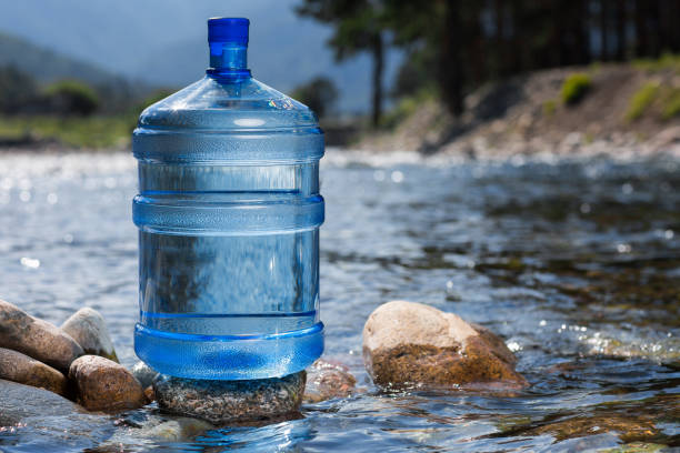 Water big bottle on mountains and rivers background Five gallon plastic water bottle gallon stock pictures, royalty-free photos & images