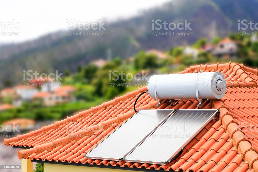 Water boiler with solar panels on roof of house stock photo