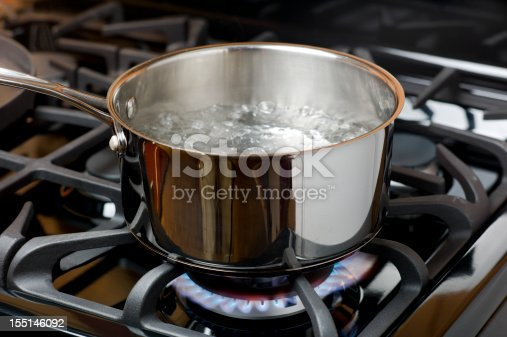 Water bubbles and boils on a gas stove or range in a home kitchen.  Blue flame and stainless steel pot.