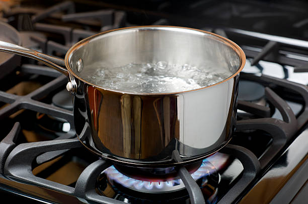 Water Boiling on a Gas Stove, stainless pot. stock photo