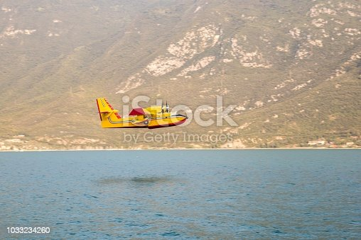 Water bomber firefighting plane over Garda Lake during forest fire in Italy