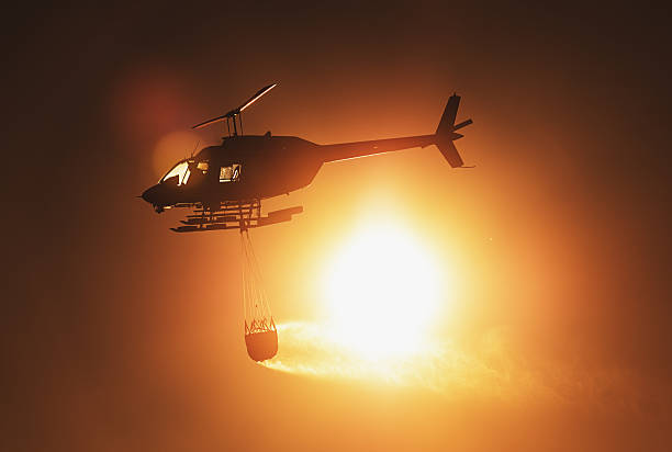Water Bombing Helicopter A helicopter is silhouetted against the Sun carrying a water bucket to a forest fire. smoke jumper stock pictures, royalty-free photos & images