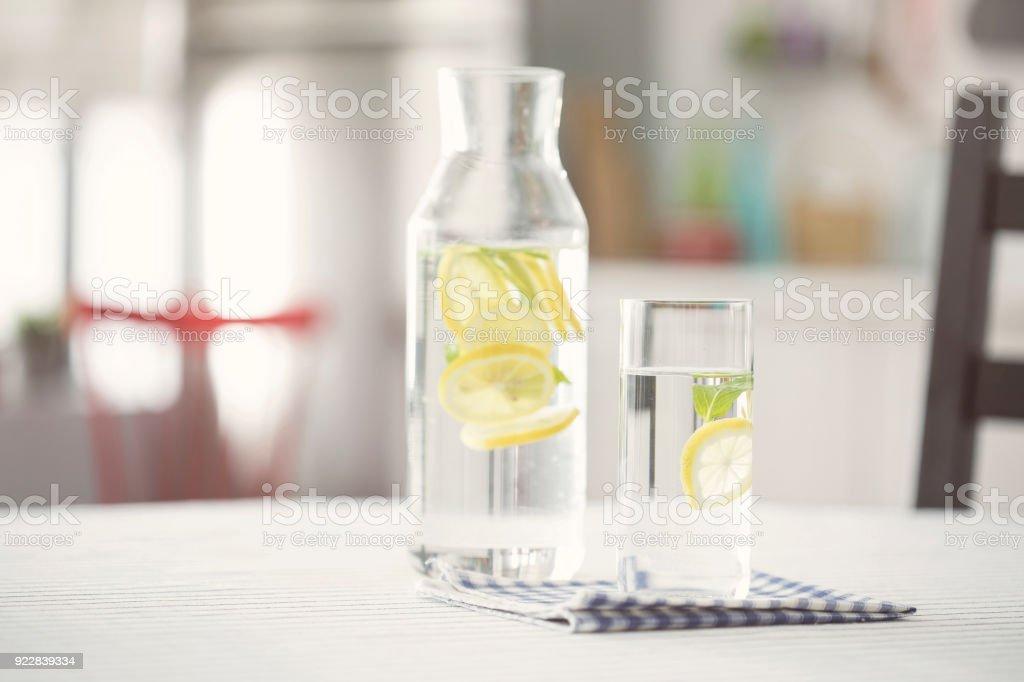 Flasche Wasser und ein Glas Wasser mit Zitrone in Küche – Foto