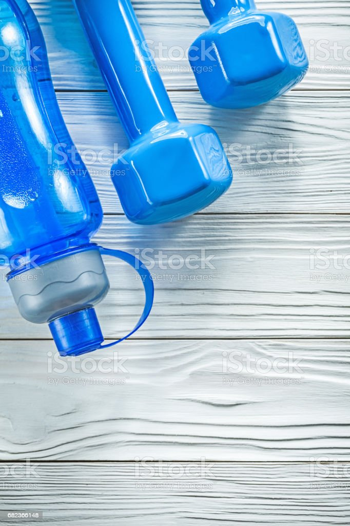 Water bottle for athletics blue dumbbells on wooden board sports royalty free stockfoto