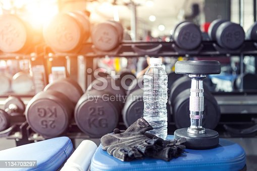 istock Water bottle in fitness gym with blurred dumbbells background. 1134703297