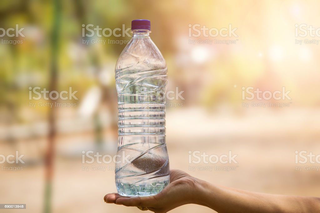 Water bottle in woman's hand on blurred green bokeh background stock photo