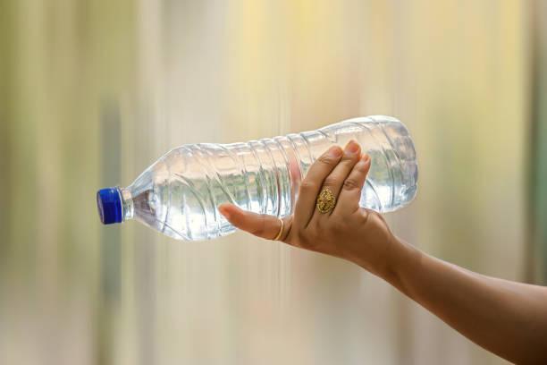 Flasche Wasser in Frauenhand auf verschwommene grüne Bokeh Hintergrund – Foto
