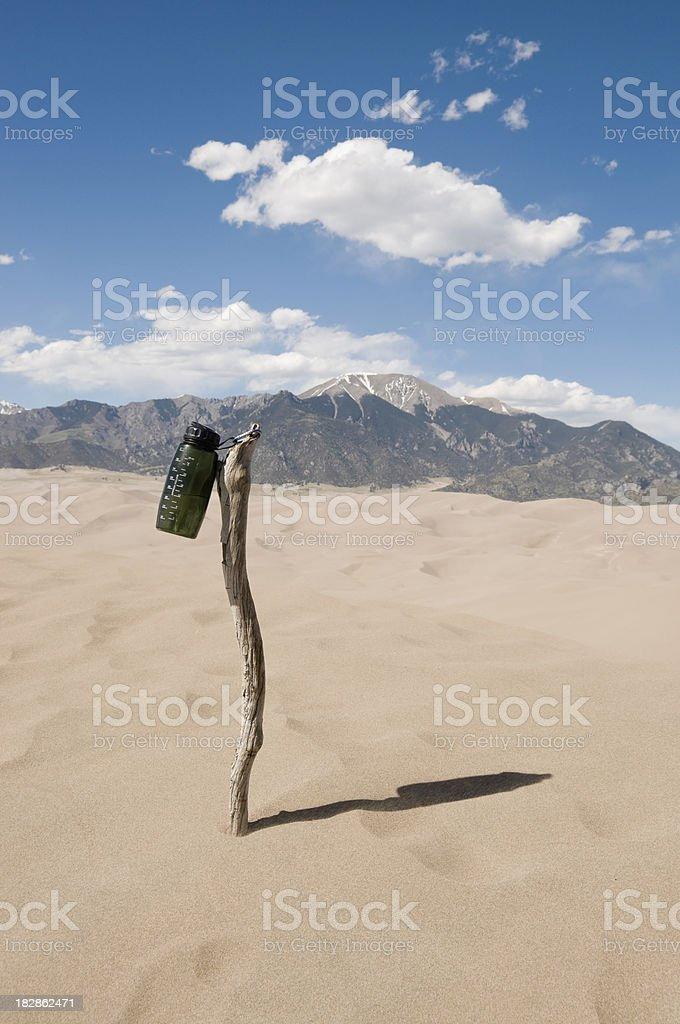 Botella de agua en un personal en el desierto seco - foto de stock