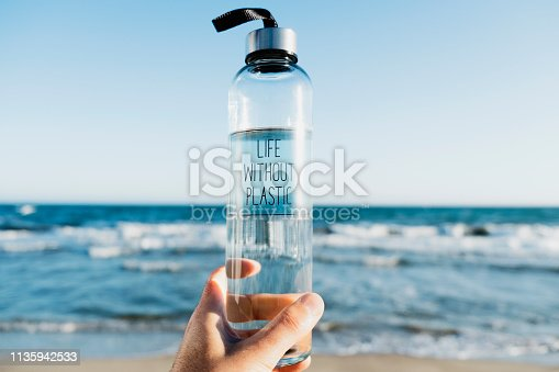 closeup of a caucasian man holding a glass reusable water bottle with the text life without plastic written in it, on the beach, with the ocean in the background