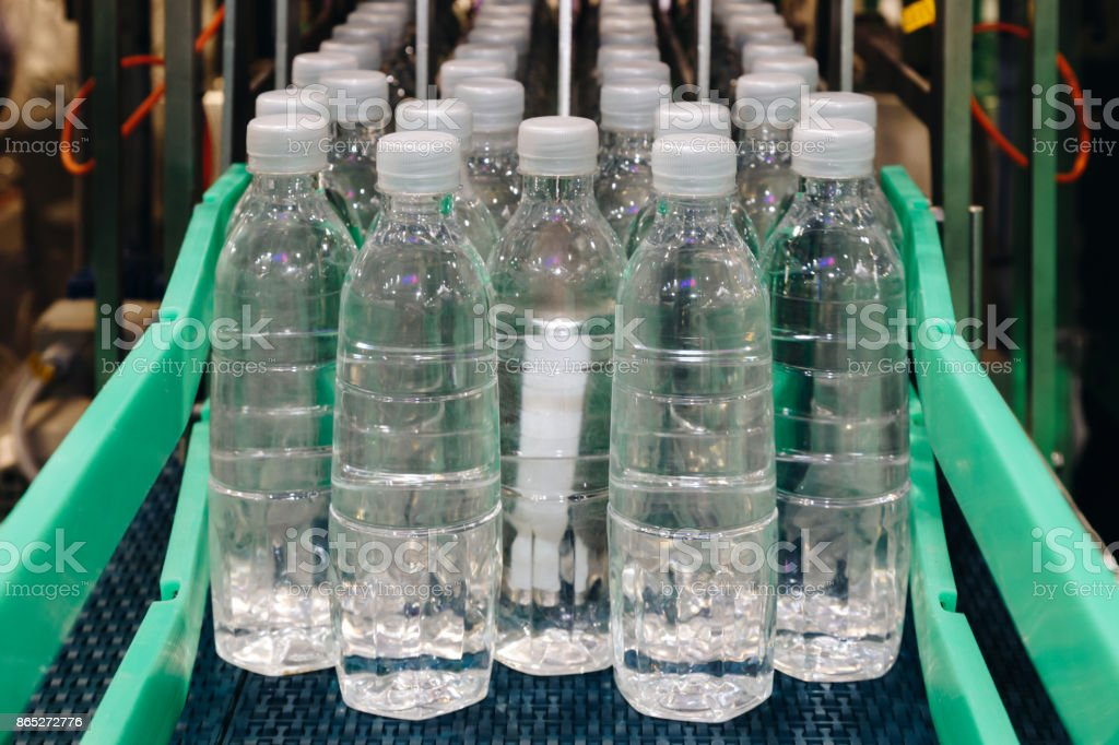 water bottling in the transparent plastic bottles at the factory line of the filling machine at the beverage manufacturing. stock photo