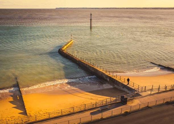 Wasserbrecher werfen Schatten auf den goldenen Strand in der späten Nachmittagssonne am West-Klippenstrand in Ramsgate, Kent UK. – Foto