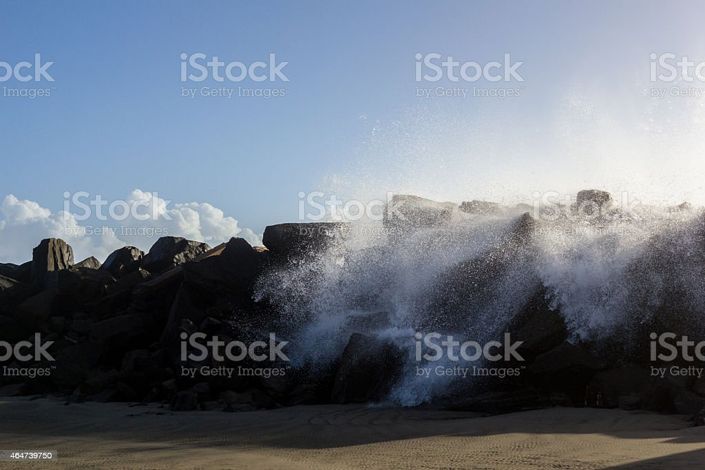 Water breaking over a rock barrier stock photo