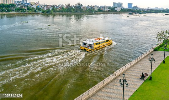 istock Water bus moving across  river to urban center. 1297342424