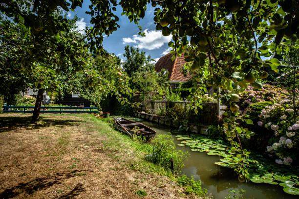 water aquaduct in oud-hollandse stad met houten vintage roeiboot, fruit boomgaard en traditionele houten huizen - beemster stockfoto's en -beelden
