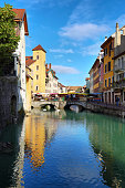 Annecy, France - June 16, 2019: colorful houses reflected in a water canal in old town of Annecy, historical city in France