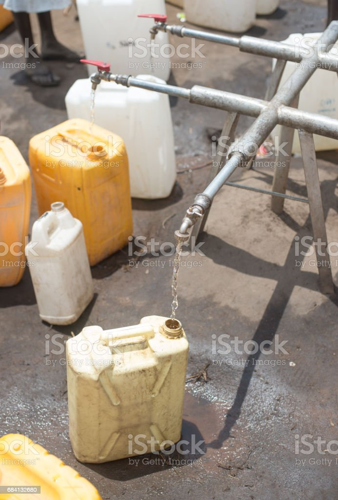 water canisters to be filled at refugee camp foto stock royalty-free