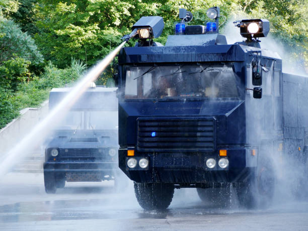 Water cannon on a police truck Police trucks with water cannons shoots a high-velocity stream of water. riot police stock pictures, royalty-free photos & images