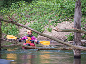 Jozefow, Poland - May  12, 2018: Water canoeing, extreme kayaking. Kayakers  in a small sport kayaks are practicing  an approach to a cascade on the Swider River in Poland